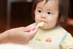 Japans babymeisje die babyvoedsel eten Royalty-vrije Stock Afbeelding