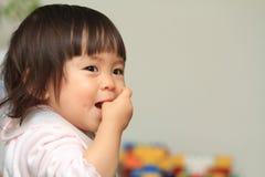Japans babymeisje die haar vinger zuigen Stock Afbeelding