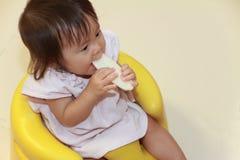 Japans babymeisje die rijstcracker eten Stock Fotografie
