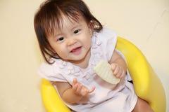 Japans babymeisje die rijstcracker eten Royalty-vrije Stock Foto
