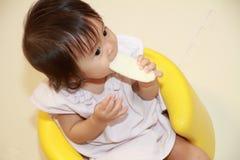 Japans babymeisje die rijstcracker eten stock foto's
