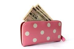 Japans bankbiljet in de roze die punt van de vrouwenportefeuille op wihtebac wordt geïsoleerd Stock Foto's