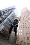 Japans meisje dat voor wolkenkrabbers springt stock foto's