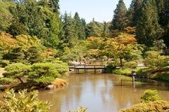 Japans tuinlandschap met vijver en brug Stock Afbeelding