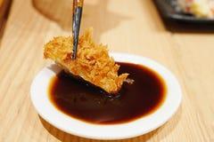 Japans voedsel, Japanse varkensvleeskotelet die Tonkatsu, eetstokjes gebruiken om een stuk van sappig varkensvlees te plukken en  royalty-vrije stock foto's