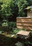 Japanse bamboemuur in openluchttuin met bomen en installaties stock afbeelding