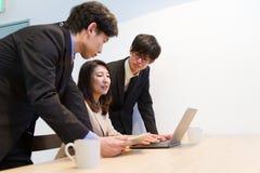 Japanse bedrijfspersoon die over documenten op laptop PC spreken royalty-vrije stock afbeelding
