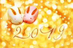 Japanse de groetkaart van 2019 met konijn gestalte gegeven gebakjes en gouden achtergrond royalty-vrije stock afbeelding