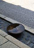 Japanse die kom met water wordt gevuld op een achtergrond van de steenvloer wordt gehouden royalty-vrije stock afbeelding