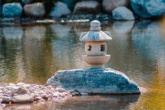 Japanse die lantaarnstandbeelden op een rots in het midden van een vijver worden geïsoleerd stock fotografie