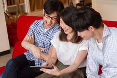 Japanse familie die elkaar spreken, die op de Internet-inhoud met tabletapparaat letten Stock Afbeelding