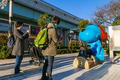 Japanse families met een standbeeld van de beeldverhaalhond voor Fuji-Televisiehoofdkwartier Stock Fotografie
