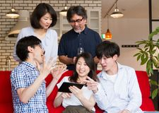 Japanse jonge en rijpe mensen die en op inhoud op Internet met tabletapparaat spreken letten royalty-vrije stock afbeeldingen