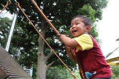Japanse jongen die op de muur beklimmen Stock Foto's