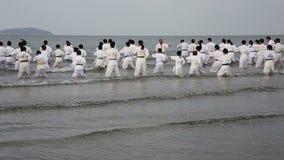 Japanse karatevechtsporten die bij het strand opleiden stock footage