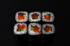 Japanse keuken, broodjes met verse zalm en komkommer, zwarte achtergrond royalty-vrije stock afbeelding
