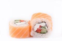 Japanse Keuken, Geplaatste Sushi: zalmbroodje met komkommer, peper en kaas op een witte achtergrond Stock Foto