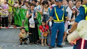 Japanse kinderen die op de uitvoerders letten bij het festival van Koenji Awa Odori stock afbeelding
