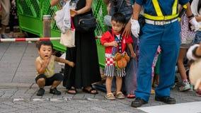 Japanse kinderen die op de uitvoerders letten bij het festival van Koenji Awa Odori stock fotografie