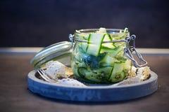 Japanse komkommersalade met zwart-witte sesamzaden in metselaarkruik met deksel op concreet rond dienblad, grijze verfraaide acht Royalty-vrije Stock Fotografie