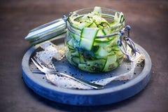Japanse komkommersalade met zwart-witte sesamzaden in metselaarkruik met deksel op concreet rond dienblad, grijze verfraaide acht Stock Foto's