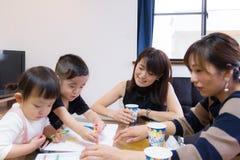 Japanse medemamma en kinderen die voedselpartij hebben en thuis van het trekken genieten Royalty-vrije Stock Foto's