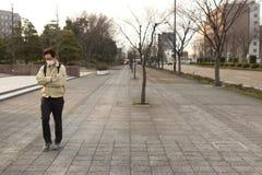 Japanse mens die alleen het dragen van een chirurgisch masker lopen royalty-vrije stock afbeeldingen