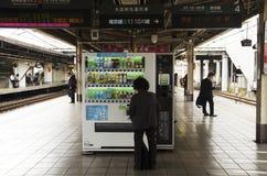 Japanse oude vrouwen die muntstuk opnemen in automatische automaat royalty-vrije stock afbeeldingen