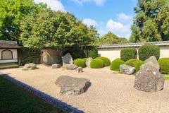 Japanse rotstuin met geharkte kiezelstenen, in orde gemaakte struiken, en insluitende muur stock afbeelding