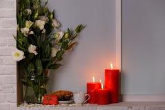 Japanse rozen in een vaas van water met ontbijt en brandende kaarsen op de vensterbank Stock Afbeeldingen
