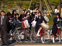 Japanse schoolmeisjes die aan school berijden Stock Afbeelding