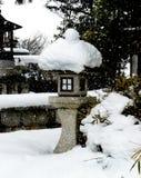 Japanse steenlantaarn in de sneeuw stock foto's