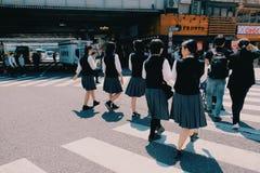 Japanse studenten die aan de school in de ochtend lopen stock foto's