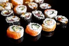 Japanse sushibroodjes op zwarte achtergrond, zijaanzicht stock foto's