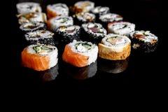Japanse sushibroodjes op zwarte achtergrond, zijaanzicht royalty-vrije stock foto's