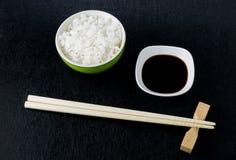 Japanse sushieetstokjes over sojasauskom, rijst op zwarte bac stock foto's