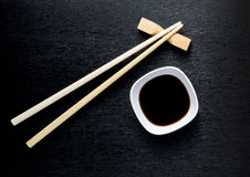 Japanse sushieetstokjes over sojasauskom, rijst op zwarte bac Stock Afbeeldingen