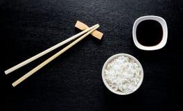 Japanse sushieetstokjes over sojasauskom, rijst op zwarte bac royalty-vrije stock fotografie