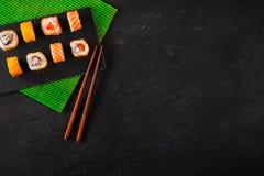 Japanse sushieetstokjes over sojasauskom, rijst op zwarte steenachtergrond Hoogste mening met exemplaarruimte royalty-vrije stock foto's