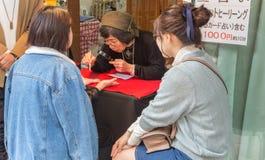 Japanse vrouw die de handlijnen lezen stock fotografie