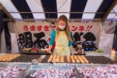 Japanse vrouw het verkopen takoyaki bij winkel op de straat aan het heiligdom van Fushimi Inari Stock Afbeeldingen