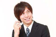 Japansk affärsman som drömmer på hans framtid Arkivbild