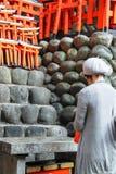Japansk dam som ber på den Fushimi Inari Taisha relikskrin arkivbild
