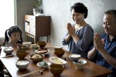 Japansk familj som äter middag samman med lycka arkivfoto
