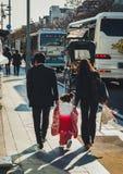 Japansk familj som går ner gatan i Kamakura Royaltyfria Bilder