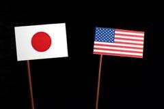 Japansk flagga med USA flaggan på svart Fotografering för Bildbyråer