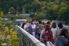Japansk flicka på den Togetsukyo bron, Arashiyama royaltyfri bild