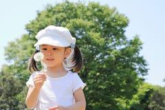 Japansk flicka som blåser maskrosfrö under den blåa himlen fotografering för bildbyråer