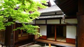 Japansk gammal träbyggnad med lönnträdet i trädgården royaltyfri foto