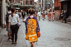 Japansk Geisha i blått och en gul kimono som går ner en gata i Gion Kyoto Japan fotografering för bildbyråer